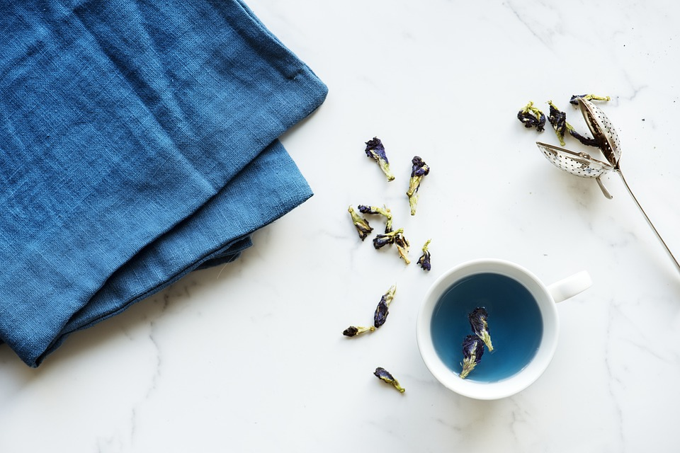 Blue tea and blue tablecloth on white marble
